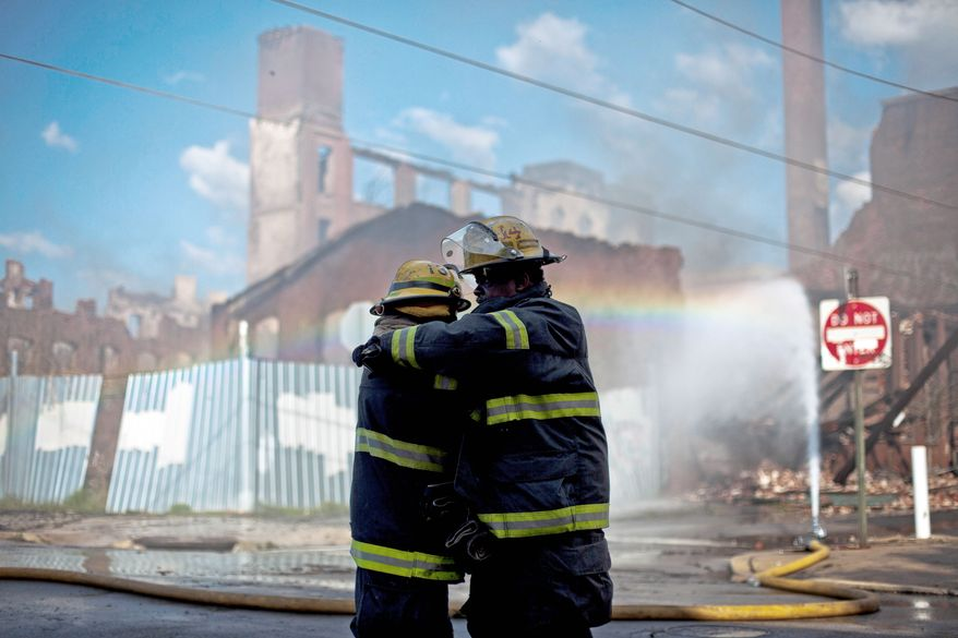 Firefighters greet each other in the aftermath of a fire Monday morning in a warehouse in Philadelphia that killed two firefighters. (Associated Press)