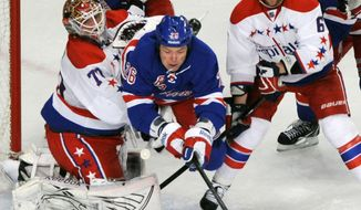New York Rangers' Ruslan Fedotenko (26) is tripped as he goes between Washington Capitals goaltender Braden Holtby, left, and Dennis Wideman, right, during the third period of an NH game on Saturday, April 7, 2012. The Caps won 4-1. (AP Photo/Bill Kostroun)
