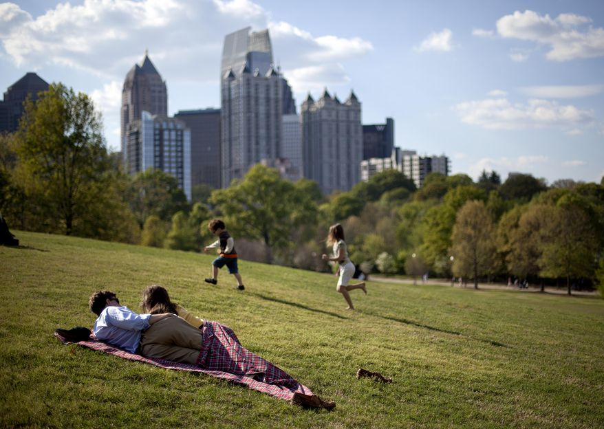 **FILE** A couple enjoy a sunny afternoon against the backdrop of the Midtown skyline from Piedmont Park in Atlanta on March 25, 2012. (Associated Press)
