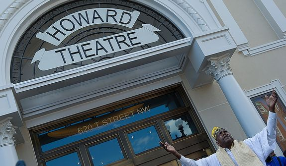 Melvin Deal, founding director of the African Heritage Dancers and Drummers, holds his arms up in praise and recognition of the ancestors following the libation offering at the grand opening of the newly renovated Howard Theatre in Washington, D.C. on Monday, April 9, 2012. (Barbara L. Salisbury/The Washington Times)
