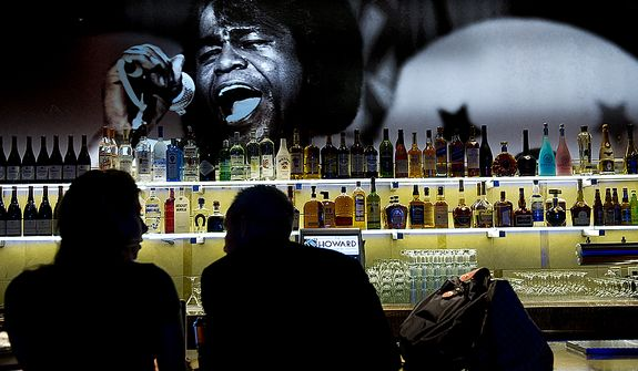 A woman and man work at the bar underneath a picture of James Brown at the newly renovated Howard Theatre on T Street Northwest in Washington, D.C. on Monday, April 9, 2012. The space is filled with photographs of the many famous acts that used to play here. (Barbara L. Salisbury/The Washington Times)
