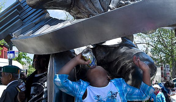 Arisemma Okrah, 5, drinks a soft drink while playing on the sculpture of Duke Ellington outside the newly renovated Howard Theatre in Washington, D.C., on Monday, April 9, 2012. (Barbara L. Salisbury/The Washington Times)