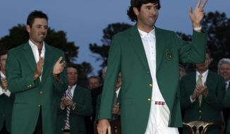 Charl Schwartzel, left, of South Africa, applauds after helping Bubba Watson put on the green jacket after winning the Masters golf tournament in a playoff Sunday, April 8, 2012, in Augusta, Ga. (AP Photo/Charlie Riedel)