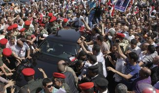 Egyptian supporters of former Egyptian Vice President Omar Suleiman surround his car as it is escorted by military police outside the Higher Presidential Elections Commission in Cairo on April 8, 2012. (Associated Press)