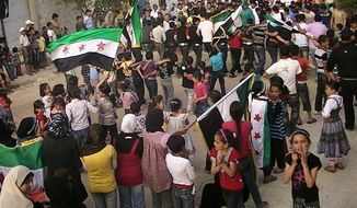 Syrians chant slogans and wave revolutionary flags during a demonstration in Daraa, Syria, on Saturday, April 7, 2012, in a photo taken by a citizen journalist. (AP Photo/Local Coordination Committees in Syria)