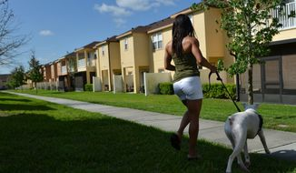 **FILE** Cheryl Brown walks her dog March 23, 2012, in the Retreat at Twin Lakes neighborhood in Sanford, Fla. The Retreat at Twin Lakes is where 17-year-old Trayvon Martin was shot and killed by neighborhood watch captain George Zimmerman on Feb. 26, 2012. (Associated Press)