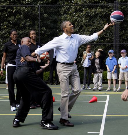 **FILE** President Obama plays basketball with former NBA player Bruce Bowen on April 9, 2012, during the annual White House Easter Egg Roll. (Associated Press)