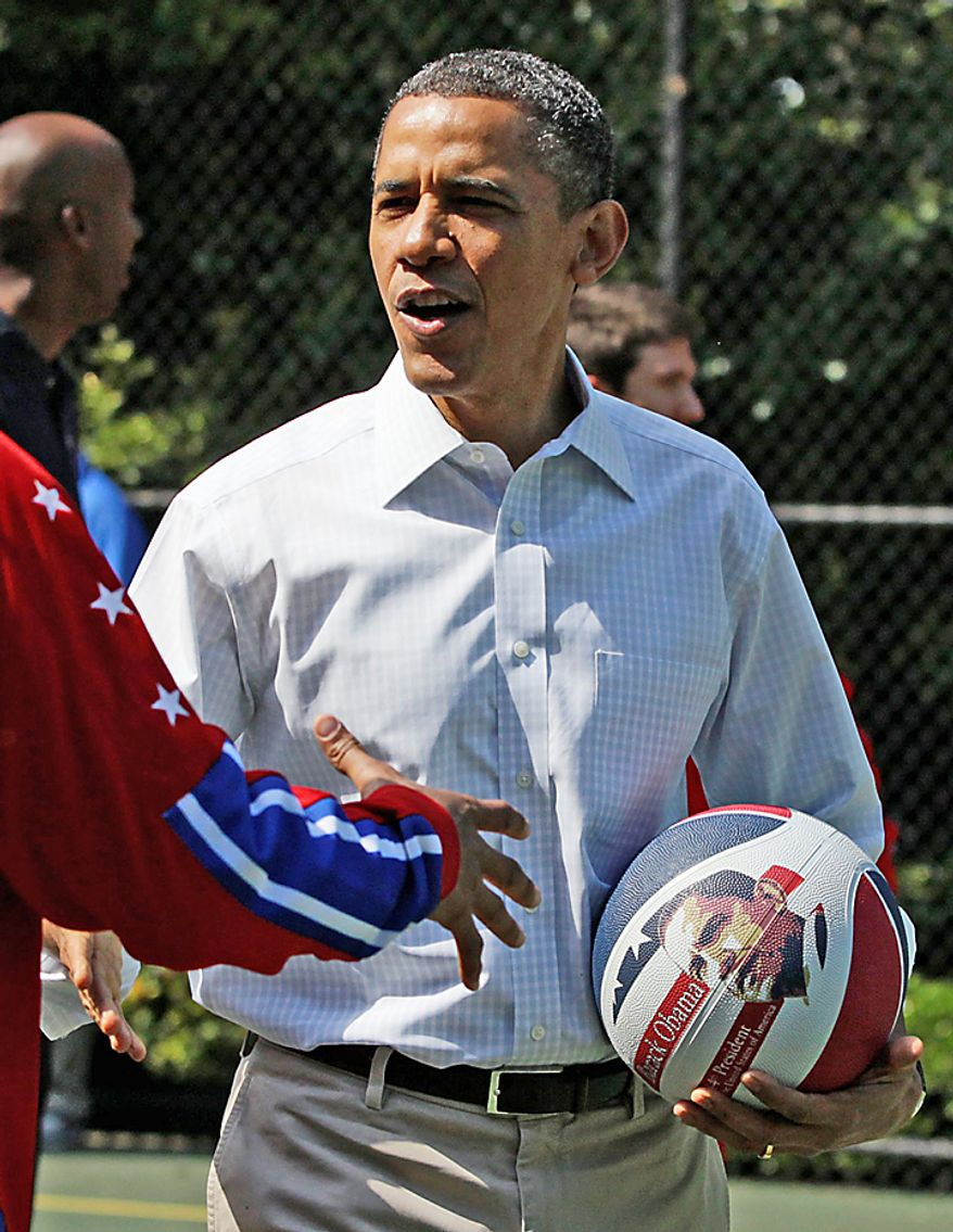 President Obama holds a basketball with his picture on it April 9, 2012, as he shakes hands with a member of the Harlem Globetrotters during the annual White House Easter Egg Roll. (Associated Press)