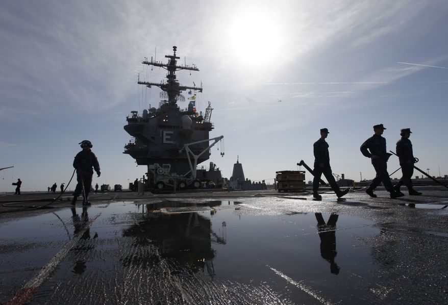 ** FILE ** U.S. sailors clean the flight deck as they move supplies and equipment in preparation for the final deployment of the nuclear aircraft carrier USS Enterprise at the Norfolk Naval Station in Norfolk, Va., on Thursday, March 8, 2012. (AP Photo/Steve Helber)