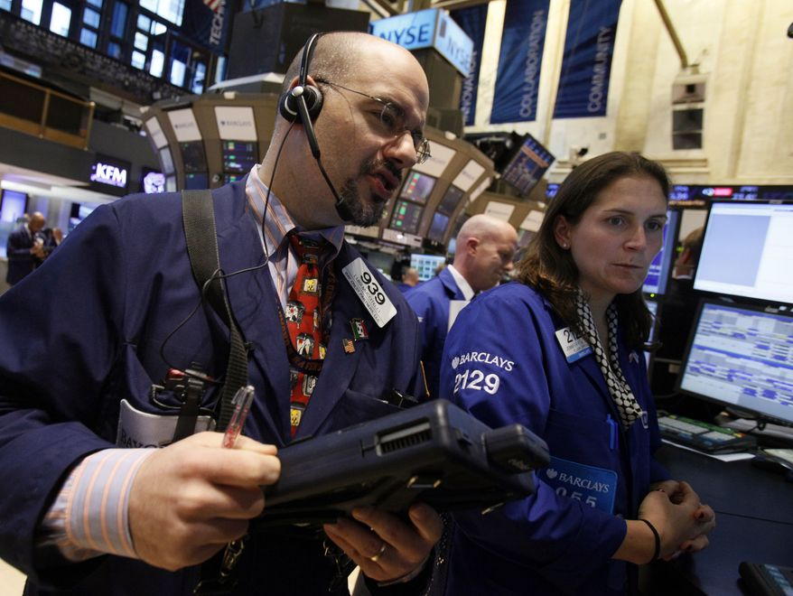 Trader Luigi Muccitelli (left) and specialist Jennifer Klesaris work on the floor of the New York Stock Exchange on Monday, April 9, 2012, in New York. (AP Photo/Richard Drew)