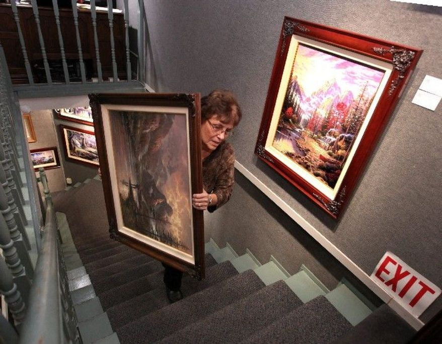"""Denice Gould, who works at the Thomas Kinkade Gallery in Placerville, Calif., moves one of the artist's works Monday. Demand has skyrocketed since the """"Painter of Light"""" died Friday. The gallery got 300 online orders in 48 hours. (Associated Press)"""