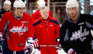 Capitals coach Dale Hunter (center) shares a light moment with captain Alex Ovechkin (left) during practice Tuesday. The Caps are hoping their recent road success continues Thursday against Boston. (Andrew Harnik/The Washington Times)