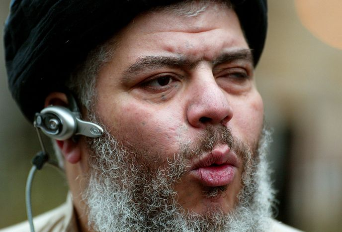 ** FILE ** Self-styled cleric Abu Hamza al-Masri leads his followers in prayer outside Finsbury Park Mosque in London in January 2004 on the first anniversary of its closure by anti-terrorism police. (AP Photo/John D. McHugh)