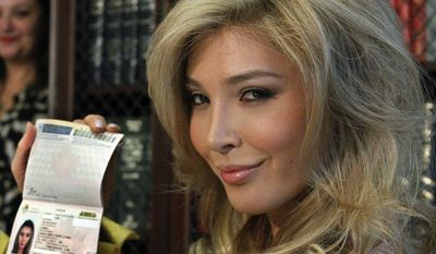"""Jenna Talackova shows her passport that lists her gender as female at an April 3, 2012, news conference in Los Angeles. Talackova, a Vancouver resident who underwent a sex change four years ago after being born a male, was initially disqualified from the 61st Miss Universe Canada pageant because she wasn't a """"naturally born"""" woman. (Associated Press)"""