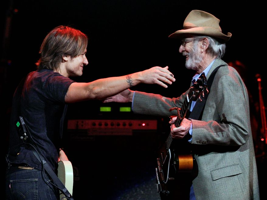 "Keith Urban (left) greets Don Williams on the stage to perform during a concert Tuesday in Nashville, Tenn. ""I heard more records in my house growing up by this guy than anybody,"" Mr. Urban said. (Associated Press)"