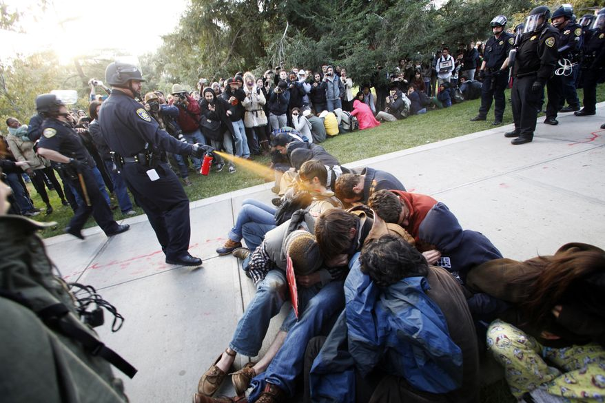 **FILE** Police Lt. John Pike uses pepper spray to move Occupy UC Davis protesters while blocking their exit from the school's quad in Davis, Calif., on Nov. 18, 2011. (Associated Press/The Enterprise)