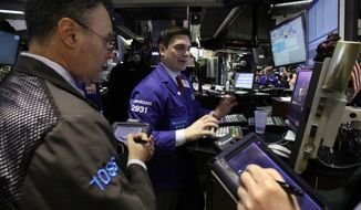 Specialist Robert Tuccillo (center) works with traders on the floor of the New York Stock Exchange on Monday, April 9, 2012. Stocks opened sharply higher on Wednesday, a day after their worst loss of the year. (AP Photo/Richard Drew)