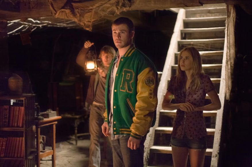 """Fran Kranz, Chris Hemsworth and Anna Hutchison (from left) check out the creepy basement of the home they've entered in """"The Cabin in the Woods."""" (Lionsgate via Associated Press)"""