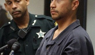 George Zimmerman stands with a Seminole County deputy during a court hearing Thursday in Sanford, Fla. He is charged with second-degree murder in the shooting death of 17-year-old Trayvon Martin. He acknowledged only his presence. (Associated Press)
