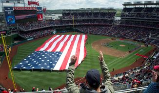 The American flag is unfurled in the outfield at Nationals Park before Washington hosted Cincinnati on Thursday in its home opener. The Nationals beat the Reds 3-2 in 10 innings. (Rod Lamkey Jr./The Washington Times)