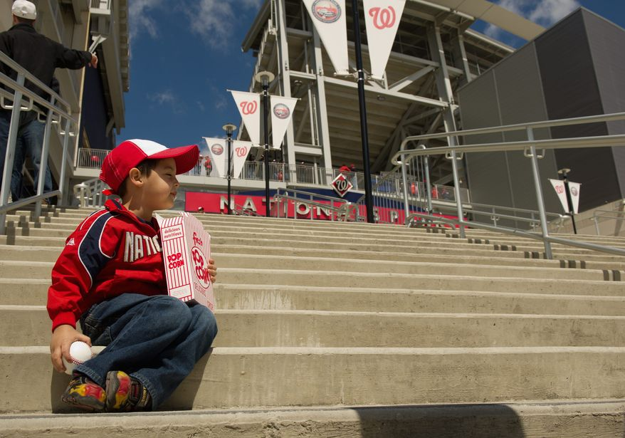 Ethan Martinez, 3, of Reston, decked out in Nationals gear, enjoys a box of popcorn outside the ballpark. (Andrew Harnik/The Washington Times)