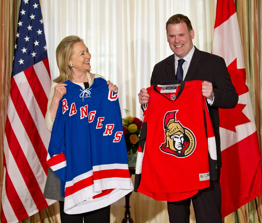 Secretary of State Hillary Rodham Clinton and Canadian Foreign Minister John Baird hold the shirts each hopes the other will wear thanks to their bet over the winner of the New York Rangers-Ottawa Senators Stanley Cup playoff series. (Associated Press)