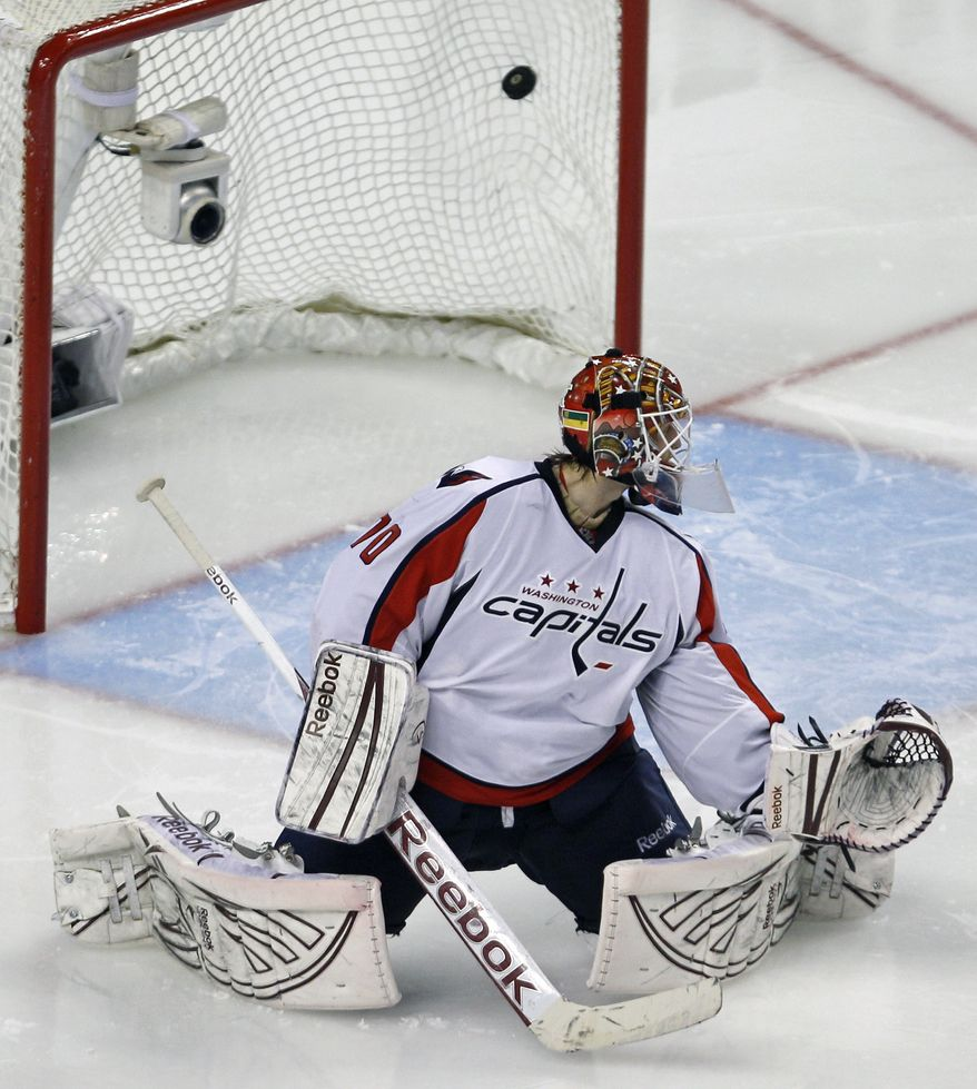 Washington Capitals goalie Braden Holtby looks back as the game-winning goal by Boston Bruins center Chris Kelly lands in the back of the net during overtime of Game 1 of the first-round playoff series in Boston on Thursday, April 12, 2012. The Bruins won 1-0. (AP Photo/Charles Krupa)