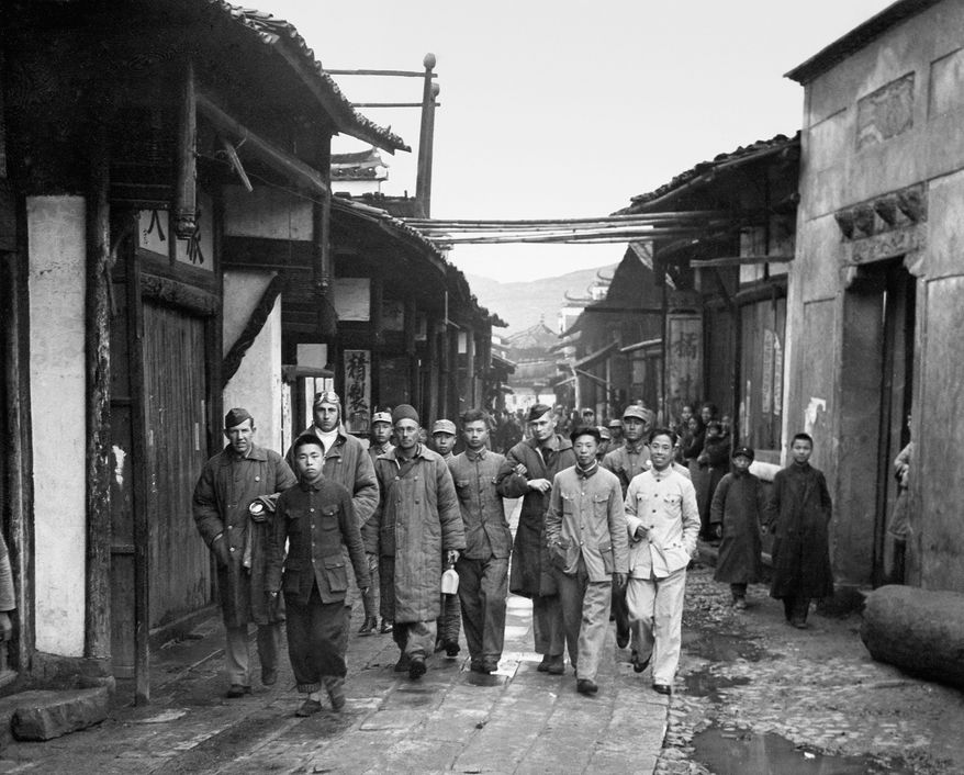 Four unidentified Doolittle crewmen who bailed out over China are escorted through a Chinese village before being reunited with others. China was a U.S. ally where the Raiders planned to reunite. (Army Air Force via Associated Press)