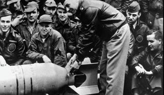 """U.S. Army Air Corps Maj. Gen. James H. """"Jimmy"""" Doolittle fastens a medal on the tail of a 500-pound bomb that his raiders dropped on Tokyo on April 18, 1942. Eighty men in 16 planes surprised the Japanese and shattered their sense of being impregnable. (Associated Press)"""