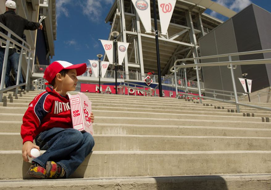 Ethan Martinez, 3, of Reston, Va., sits on steps leading into Nationals Park. (Andrew Harnik/The Washington Times)