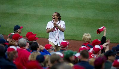 A man stands on the dugout and leads the crowd in a cheer. (Rod Lamkey Jr/The Washington Times)