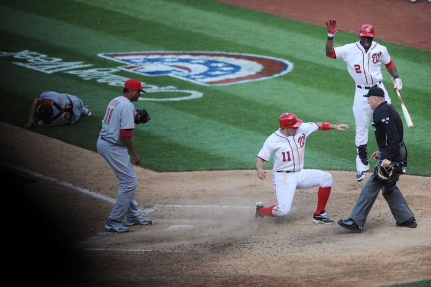 Washington Nationals outfielder Roger Bernadina (2) runs to greet third baseman Ryan Zimmerman (11) as he scores the winning run on a wild pitch in the bottom of the 10th inning. (Rod Lamkey Jr/The Washington Times)