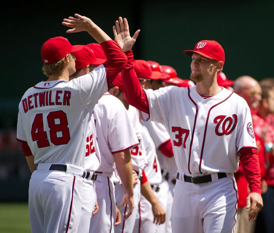 Washington Nationals starting pitcher Ross Detwiler (48), left, high fives Washington Nationals starting pitcher Stephen Strasburg (37), right, before the Washington Nationals defeat the Cincinnati Reds in extra innings, 3-2, for their home opener in Major League Baseball at Nationals Park, Washington, D.C., Thursday, April 12, 2012. (Andrew Harnik/The Washington Times)