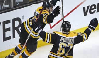 Boston Bruins center Chris Kelly (23) celebrates his game-winning goal against the Washington Capitals with teammate Benoit Pouliot in overtime of the first-round playoff series in Boston on Thursday, April 12, 2012. The Bruins won 1-0. (AP Photo/Charles Krupa)