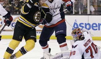 Washington Capitals defenseman John Carlson keeps Boston Bruins center David Krjejci away from the loose puck. The Capitals used their bodies to block shots and clear the crease area during their 1-0 overtime loss in Game 1 of their first-round series on Thursday, April, 12, 2012. (AP Photo/Elise Amendola)