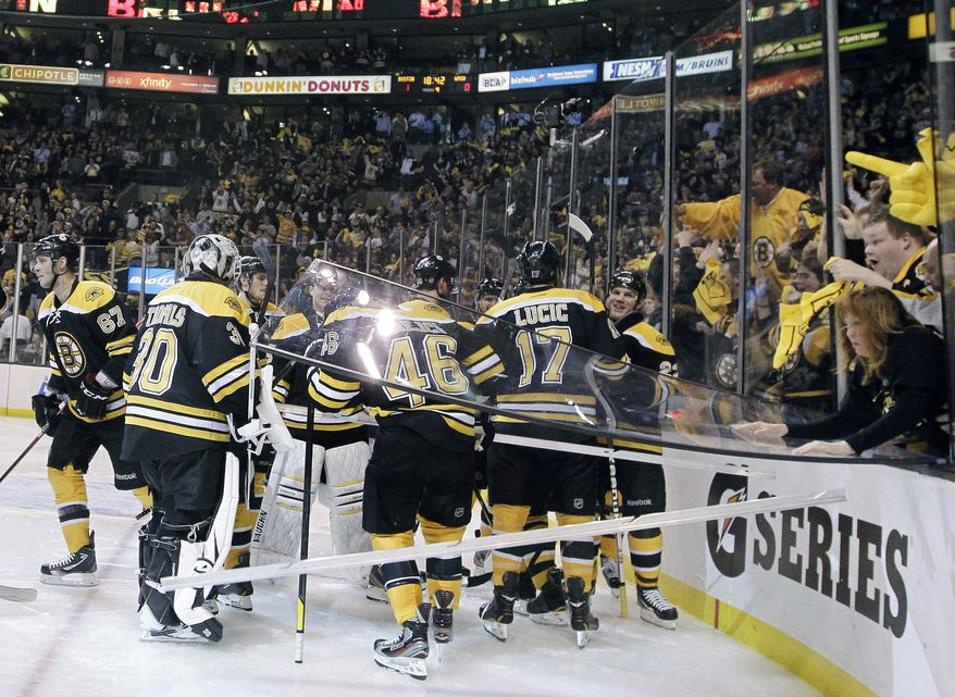 A glass pane falls out onto Boston Bruins center David Krejci (46) as Bruins players and fans celebrate their 1-0 victory in overtime against the Washington Capitals in Game 1 their first-round series in Boston on Thursday, April 12, 2012. (AP Photo/Elise Amendola)