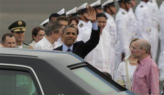 President Barack Obama waves upon arrival to Cartagena, Colombia, Friday April 13, 2012. Obama is in Cartagena to attend the sixth Summit of the Americas. At right is U.S. ambassador to Colombia Michael McKinley. (AP Photo/Dolores Ochoa)