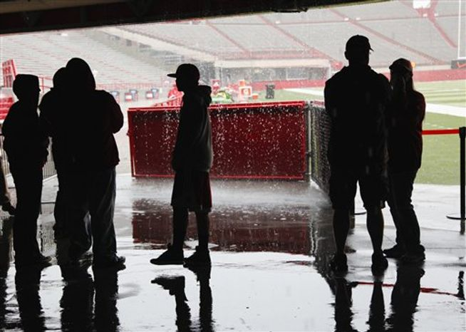 Nebraska fans at Memorial Stadium in Lincoln, Neb., take cover from the rain prior to the cancellation of the annual Red-White college football Game, Saturday, April 14, 2012. Nebraska has canceled its spring football game because of heavy rain, hail and sharp lightning which began moving through the area about 90 minutes before the scheduled kickoff Saturday. (AP Photo/Nati Harnik)
