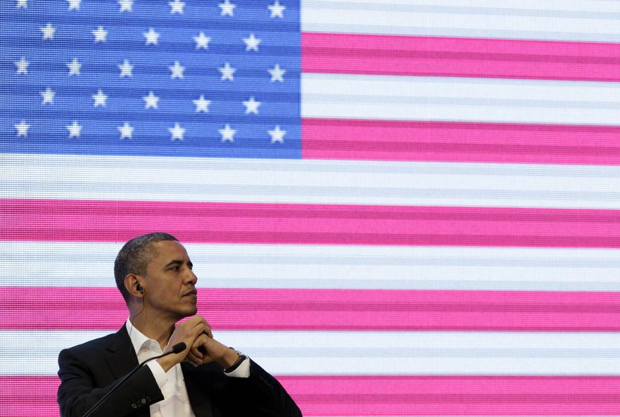 President Barack Obama sits in front of a large video screen displaying an image of a U.S. national flag at the CEO Summit of the Americas, in Cartagena, Colombia, Saturday April 14, 2012. (AP Photo/Carolyn Kaster)