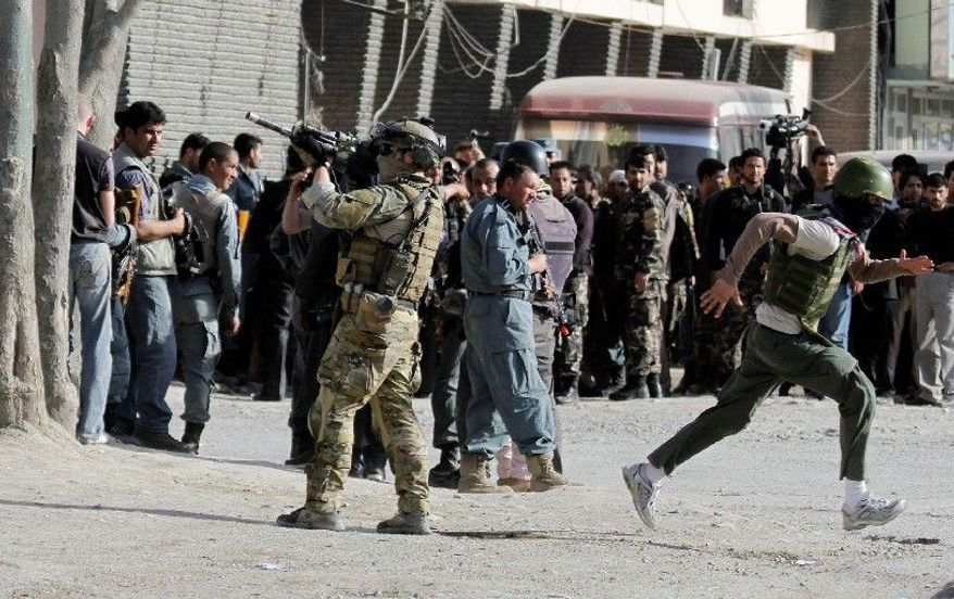 A NATO soldier is poised to respond at the scene of an attack by the Taliban in Kabul, Afghanistan, on Sunday. At least two Taliban were killed and five people were wounded in the capital. There were attacks in three other cities. (Associated Press)