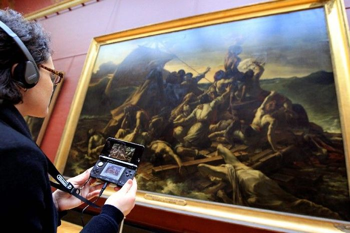 """A visitor studies """"The Raft of the Medusa"""" by Theodore Gericault with the help of the new audio guide at the Louvre Museum in Paris on Thursday. (Associated Press)"""