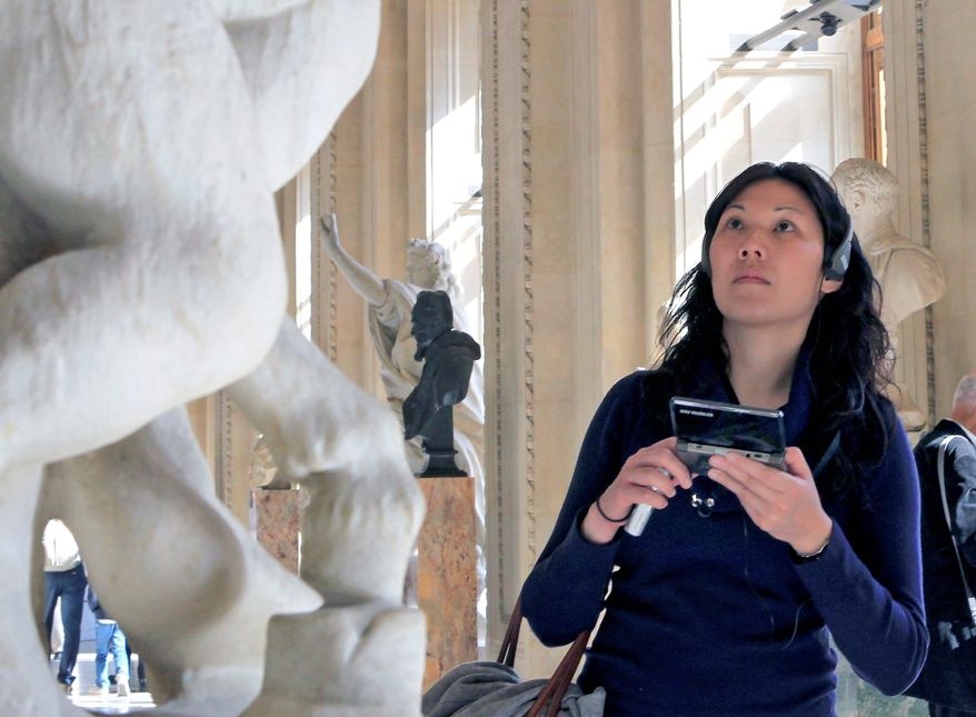 A visitor views a sculpture at the Louvre Museum in Paris with the help of the new audio guide on Thursday. The famed Paris museum is going 3D visual with its electronic guides in a deal with Japan's Nintendo to provide game consoles to help visitors who navigate its labyrinthine halls by the millions each year. (Associated Press)