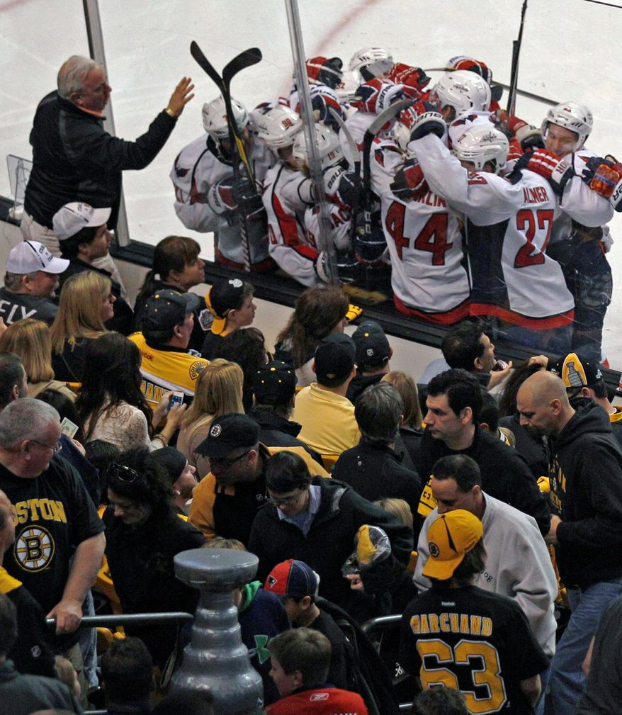 Boston Bruins fans watch as Washington Capitals center Nicklas Backstrom is surrounded by teammates after his game-winning goal during the second overtime period of Game 2 of an NHL hockey Stanley Cup first-round playoff series in Boston, Saturday, April 14, 2012. The Capitals won 2-1, tying the series at 1-1. (AP Photo/Charles Krupa)