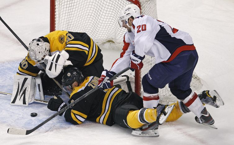 Washington Capitals left wing Troy Brouwer (20) reaches for the puck as Boston Bruins goalie Tim Thomas (30) misses the save for the first goal of the game during the second period of Game 2 of an NHL Stanley Cup first-round playoff series in Boston, Saturday, April 14, 2012. (AP Photo/Charles Krupa)