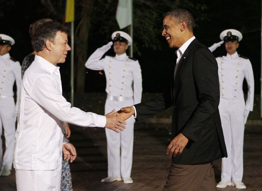 President Obama (right) shakes hands with Colombian President Juan Manuel Santos during a dinner at the sixth Summit of the Americas in Cartagena, Colombia, on Saturday, April 14, 2012. (AP Photo/Fernando Llano)