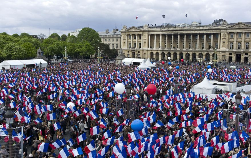 Supporters of French President Nicolas Sarkozy, who is running for re-election, wave French flags during a campaign rally at the Place de la Concorde in Paris on Sunday, April 15, 2012. (AP Photo/Thibault Camus)
