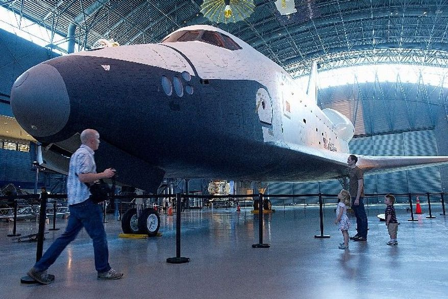 Getting a last look at Space Shuttle Enterprise are (from left) Jonathan Featherstone of Oakton, his children Emmie, 4, and Luke, 2, and his brother, Michael, at the Smithsonian's Stephen F. Udvar-Hazy Center in Chantilly. (Barbara L. Salisbury/The Washington Times)
