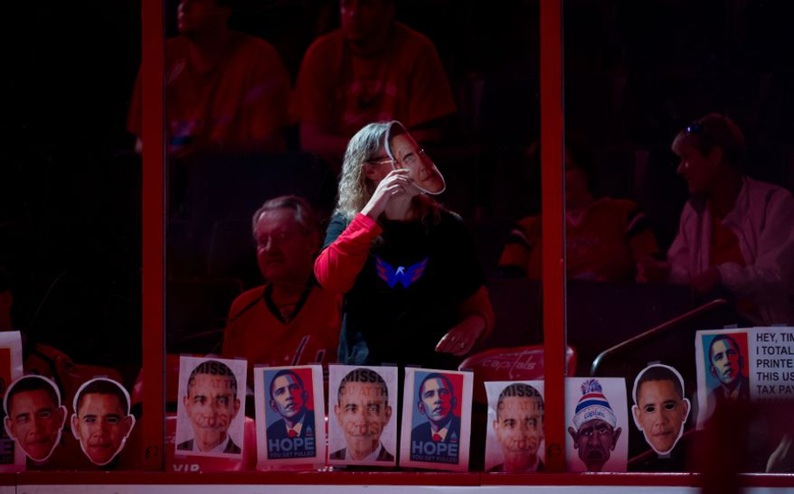Capitals fan Judi Miller of Kensington, Md., center, wears a cut out of President Obama to taunt Boston Bruins goalie Tim Thomas (30), during warm ups before the Washington Capitals take on the Boston Bruins in game three of National Hockey League first round playoff hockey at the Verizon Center, Washington, D.C., Monday, April 16, 2012. (Andrew Harnik/The Washington Times)