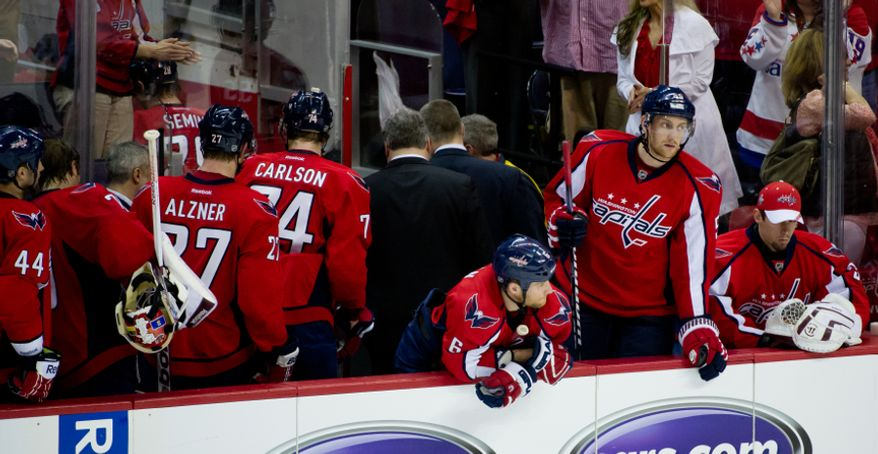 Washington Capitals defenseman Dennis Wideman (6), third from right, and Washington Capitals defenseman Jeff Schultz (55), second from right, look out on the ice as their teammates head back to the locker room after the Washington Capitals lose to the Boston Bruins in game three, 3-4, of National Hockey League first round playoff hockey at the Verizon Center, Washington, D.C., Monday, April 16, 2012. (Andrew Harnik/The Washington Times)