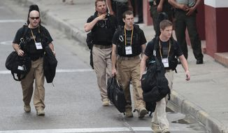 U.S. Secret Service agents walk April 14, 2012, around the Convention Center in Cartagena, Colombia, prior to the opening ceremony of the 6th Summit of the Americas. (Associated Press)